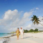 Senior couple walking on beach with coconut palm tree