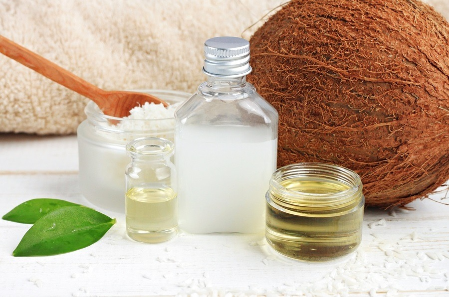 Coconut oil products cosmetic use. Skincare benefits. Bottles coconut oil, coconut milk, shavings.