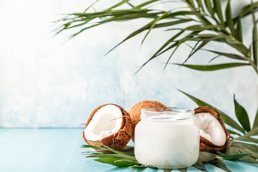 Coconut oil and coconuts on a bright pastel background, selective focus.