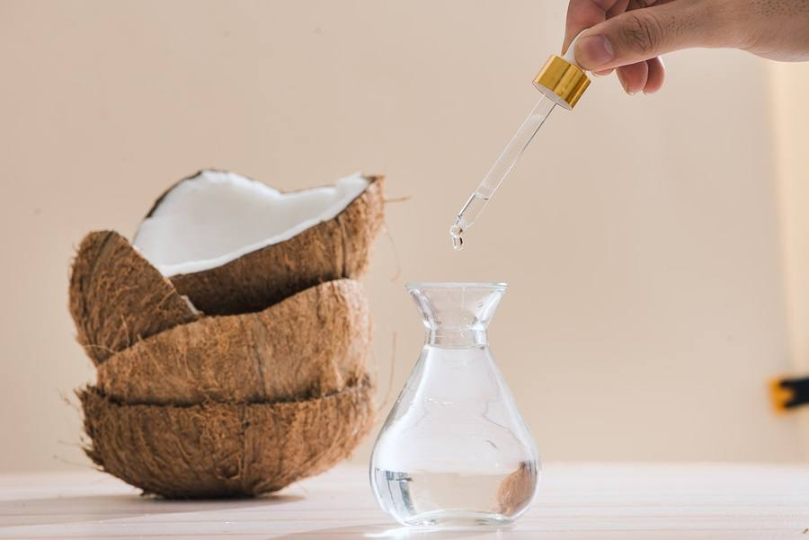 Healthy skincare. Pure coconut oil is made from organic coconut on wooden background