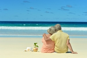 Elderly-couple-sitting-on-beach-coconut-300x200